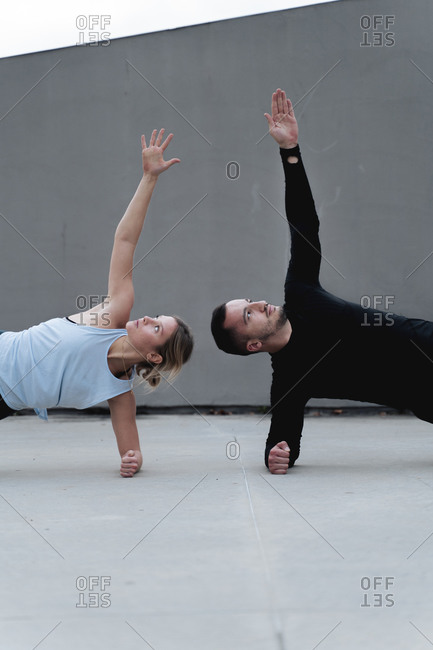 Couple stretching arms while doing side plank pose against wall