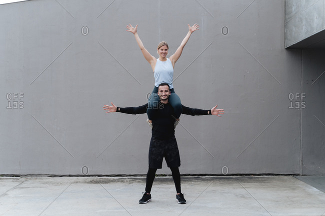 Woman with hand raised sitting on man shoulder standing with arms outstretched against wall