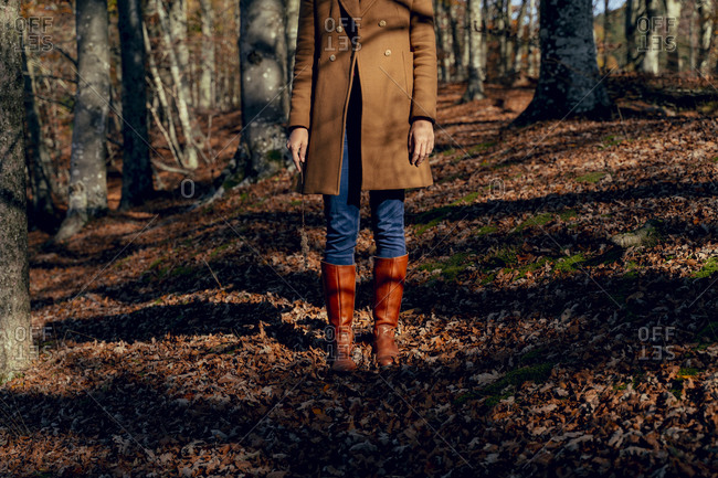Woman wearing jacket and rubber boot standing on fallen leaf in forest