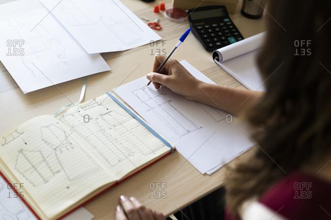Creative female professional sketching design on paper at studio