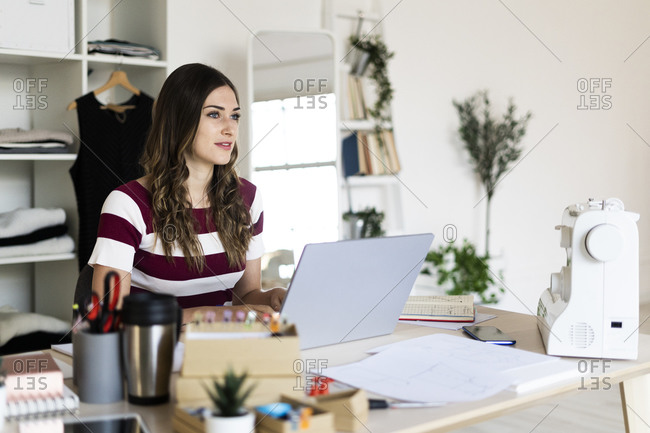 Beautiful female fashion designer looking away while sitting with laptop in studio