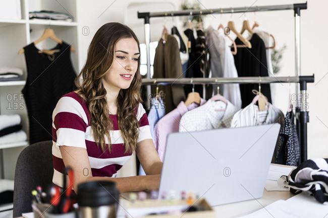 Female design professional working on laptop at studio