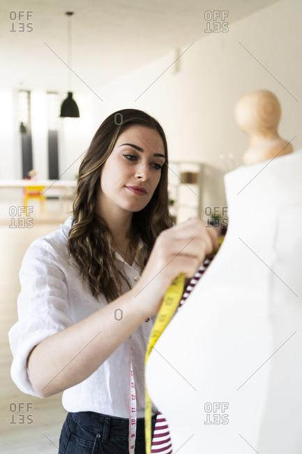 Beautiful female designer measuring fabric on mannequin at studio