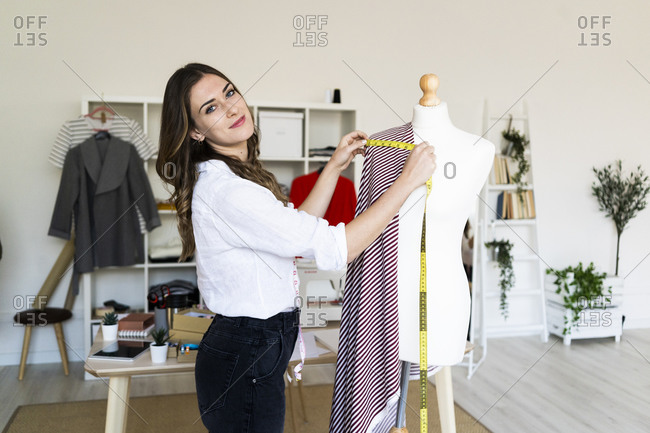 Young female creative professional measuring fabric on mannequin while standing at studio