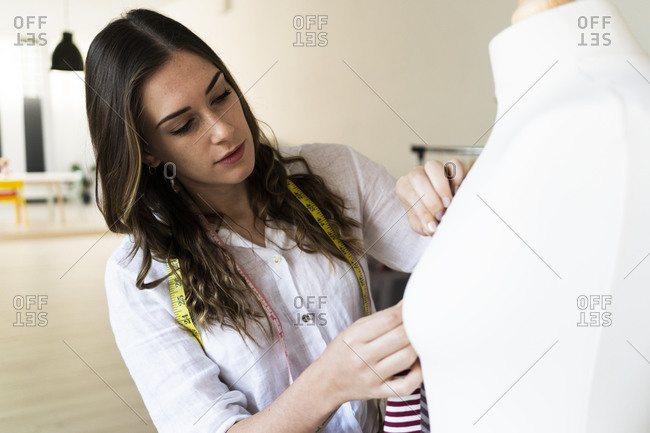 Young female designer adjusting fabric on mannequin while standing at studio