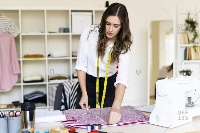 Young creative designer measuring fabric kept on desk at studio