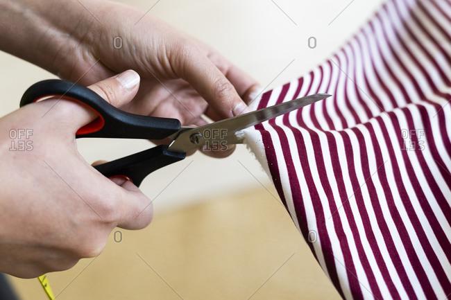 Female designer's hand cutting fabric in studio