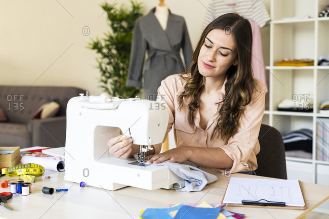Smiling young female creative professional using sewing machine while sitting at studio