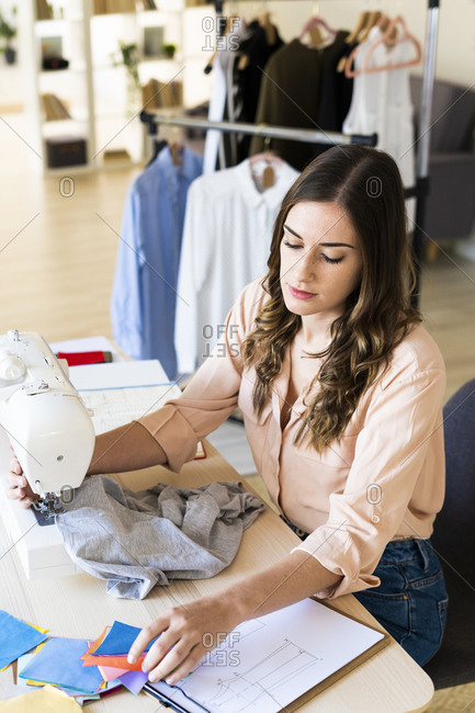 Young female fashion designer looking at fabric swatches while sewing on machine in studio
