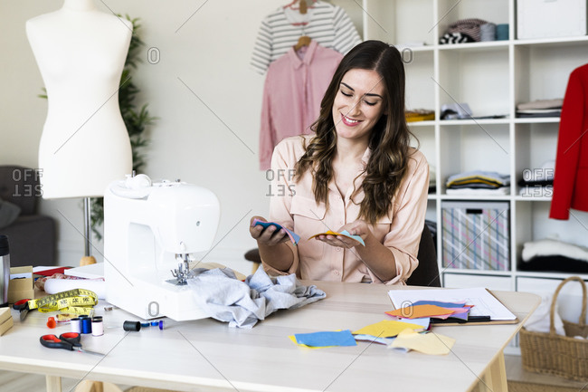 Smiling female designer analyzing fabric swatches while sitting in studio
