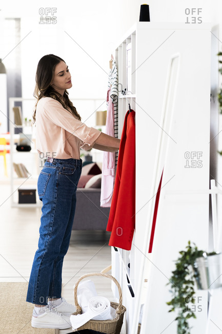 Young female designer keeping clothes in rack at studio