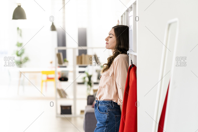 Female fashion designer with eyes closed leaning on rack at studio