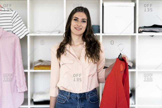 Smiling female designer holding red winter coat while standing against rack in studio