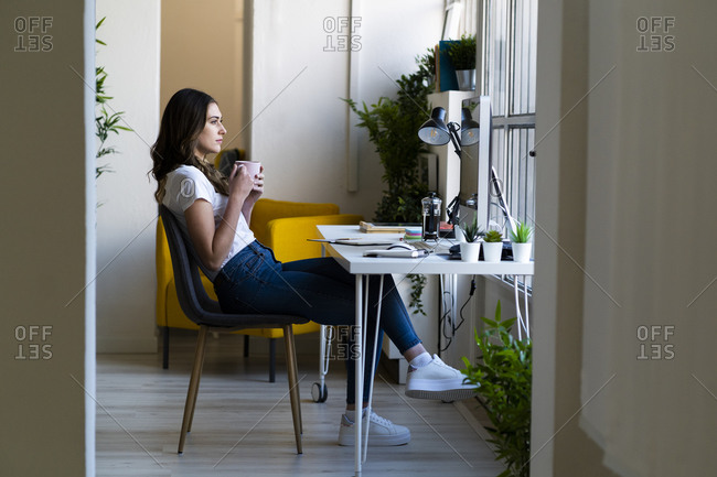 Thoughtful businesswoman holding coffee cup while sitting on chair at office