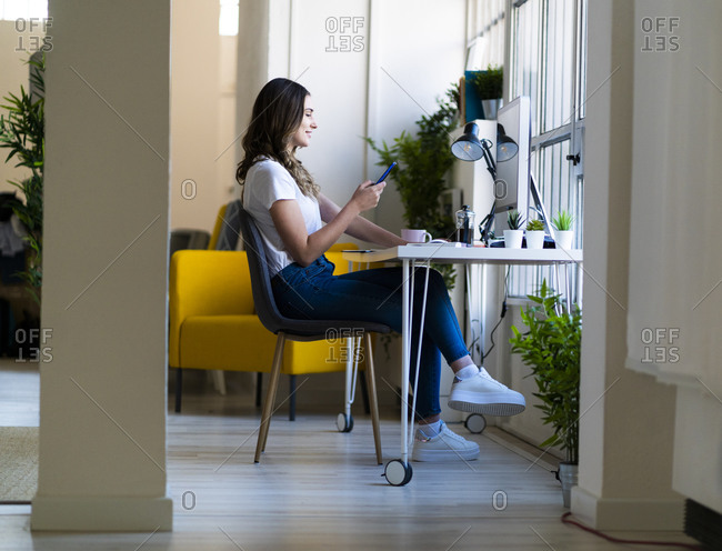 Young businesswoman using smart phone while sitting in office