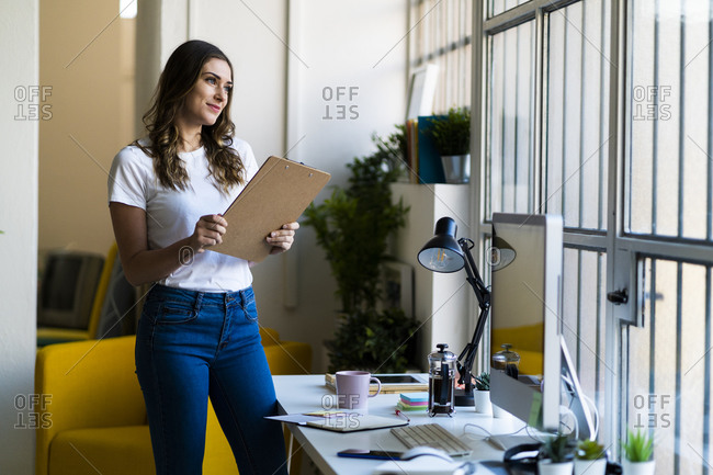 Smiling businesswoman holding clipboard while looking away in office
