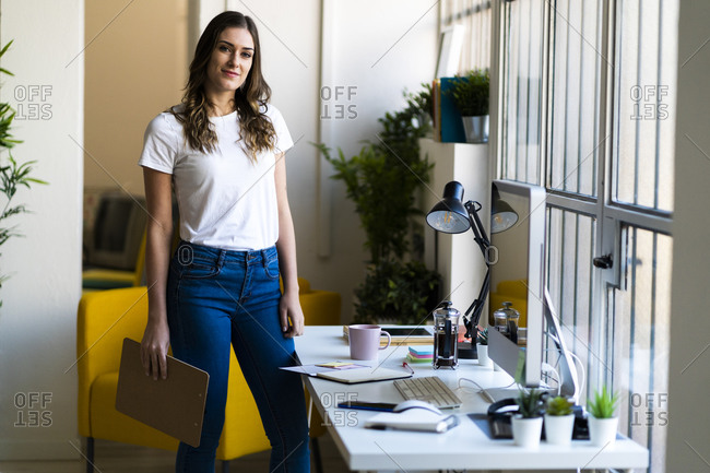 Young businesswoman holding clipboard while standing at office