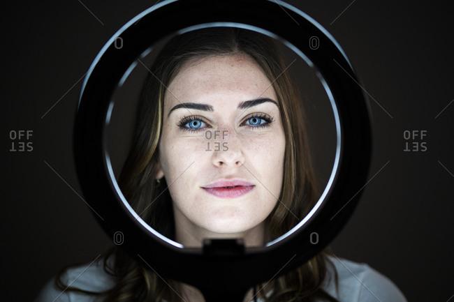 Beautiful young woman looking through illuminated ring light at studio