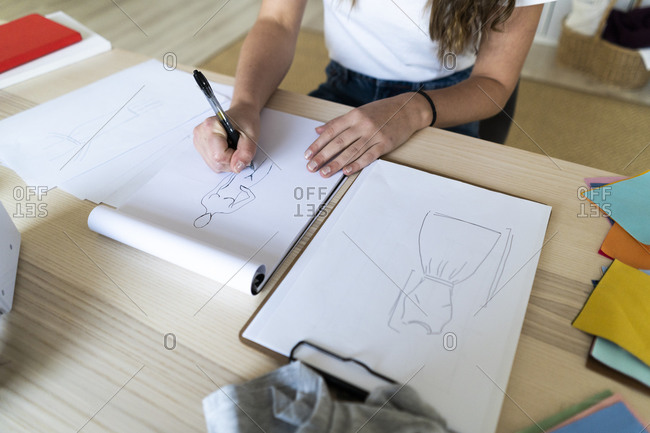 Young female fashion designer sketching design in book at studio