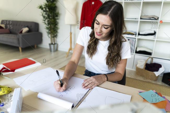 Smiling female fashion designer drawing sketch in book at studio