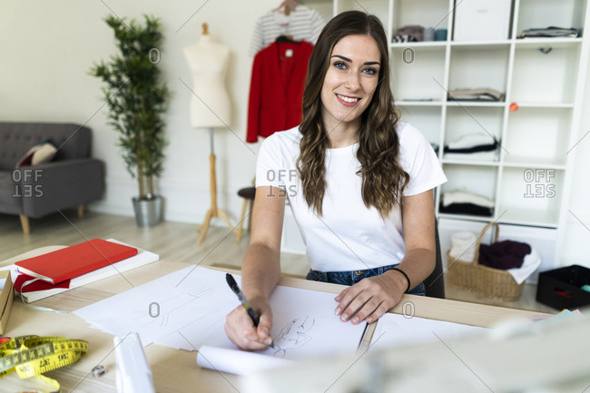 Creative female professional smiling while drawing sketch in book at studio