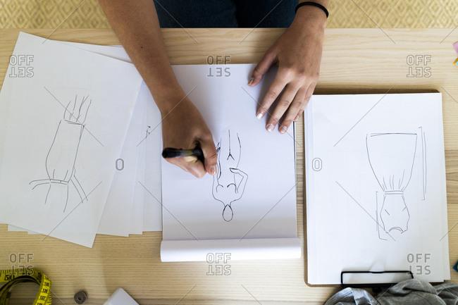 Female designer's hand drawing sketch in book at studio