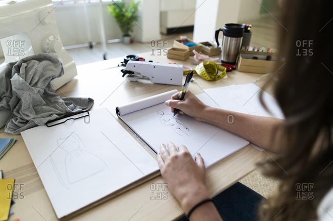Young female creative designer sketching design in book at studio