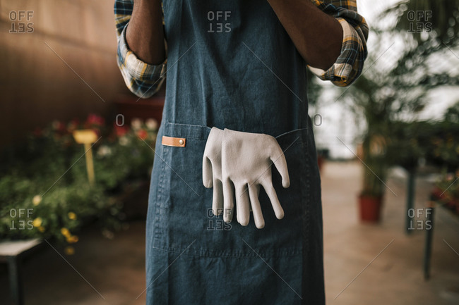 Young botanist wearing apron with glove hanging from pocket at garden center