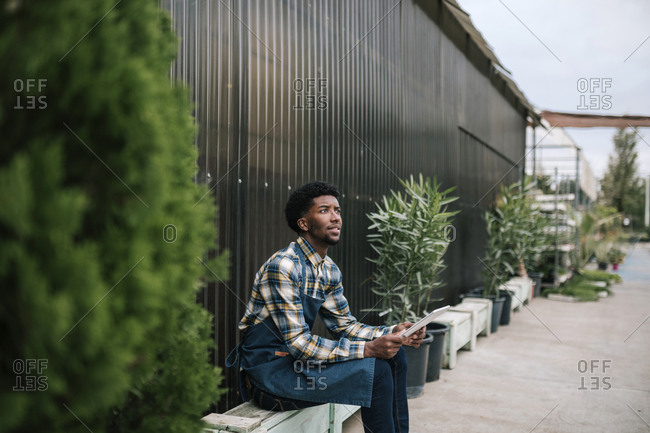 Young male worker holding digital tablet while looking away sitting against corrugated wall