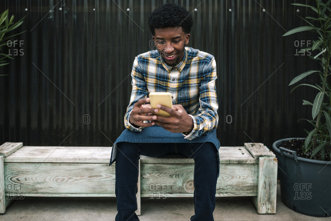 Smiling male farm worker using mobile phone while sitting on bench against corrugated wall