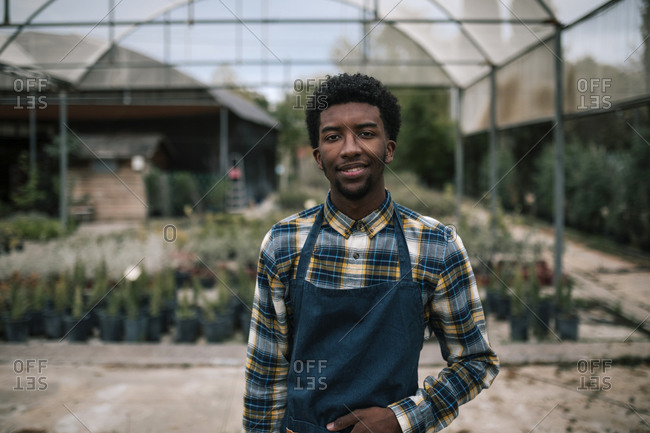 Smiling young farm worker standing against greenhouse