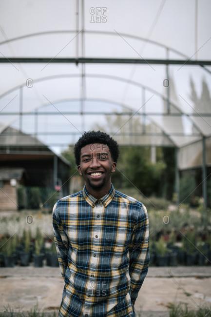 Happy male farm worker standing in garden center