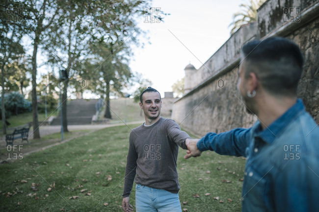 Man holding hand of boyfriend while standing at public park
