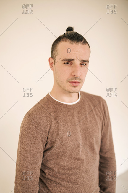 Young gay man in brown t-shirt standing against beige background