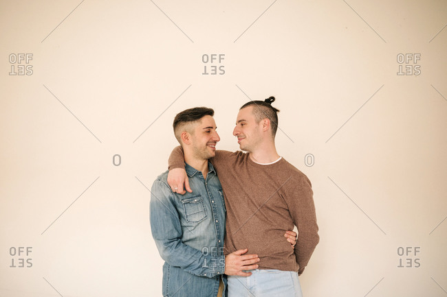 Happy gay couple with arm around standing against beige background