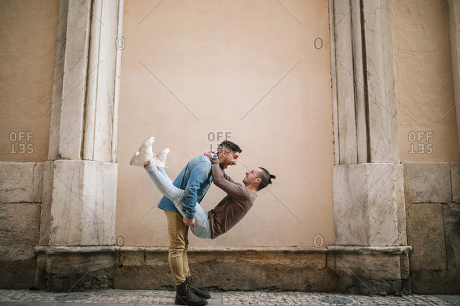 Playful gay couple spending happy time by wall