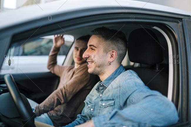 Smiling gay men sitting in car