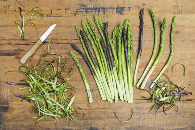 Kitchen knife and freshly peeled asparagus stalks