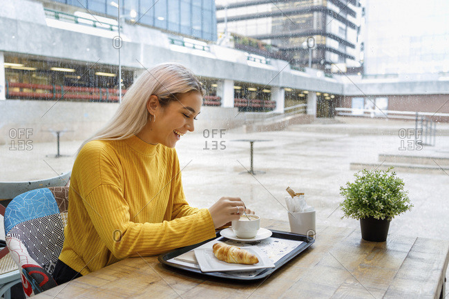 Happy young woman having breakfast at cafe during rainy season