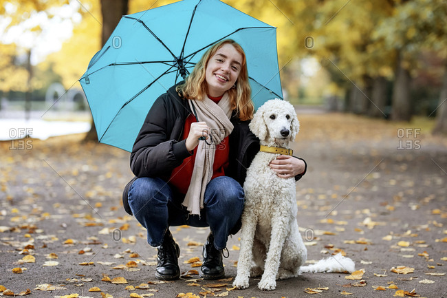 Smiling teenage girl holding umbrella while crouching by pet on road at park