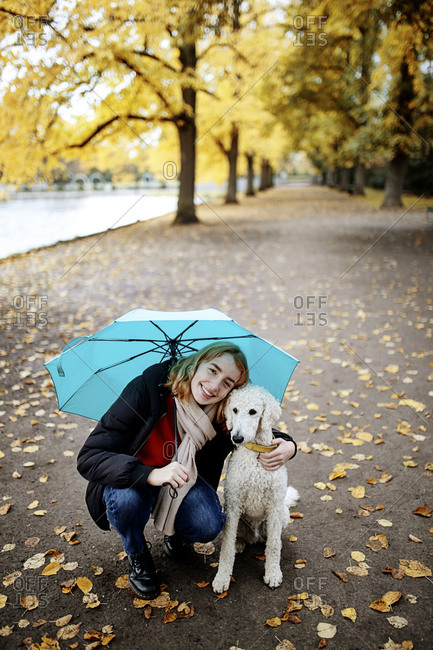 Smiling teenage girl with umbrella embracing poodle while crouching on road at park
