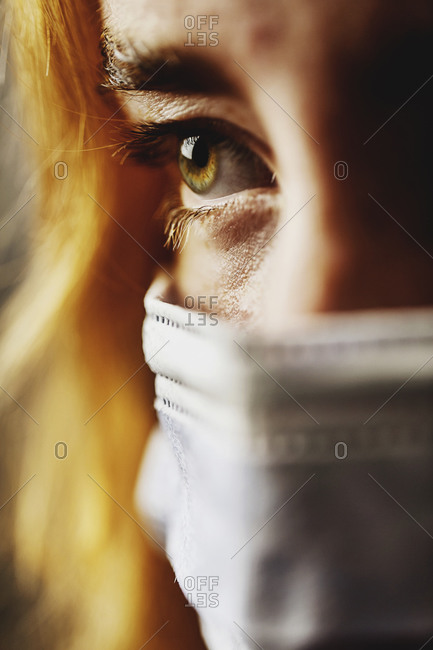 Close-up teenage girl eye wearing protective face mask on face