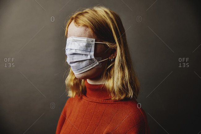 Blond girl wearing protective face mask on face while standing against gray background
