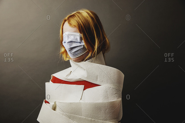 Teenage girl wrapped in toilet paper and face covered with protective face mask standing against gray background