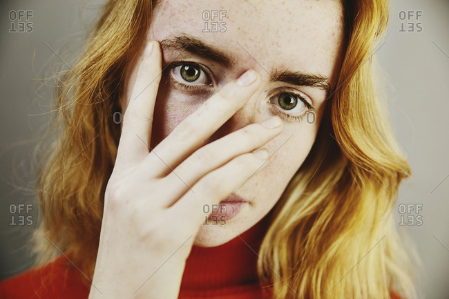 Blond teenage girl covering face with hand