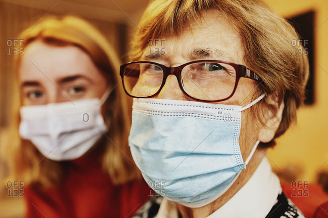 Grandmother wearing face mask and eyeglasses staring while sitting by granddaughter at home