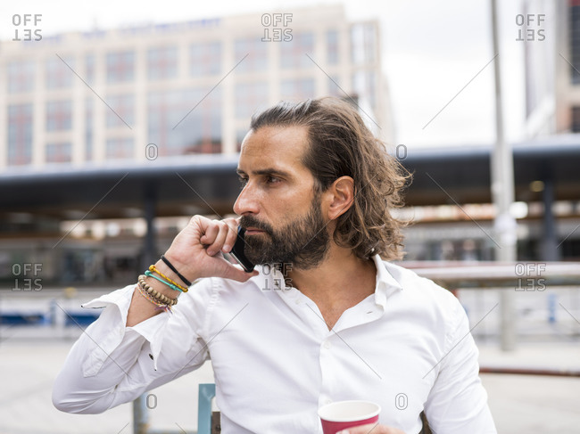 Candid portrait of bearded businessman sitting outdoors and talking on smart phone