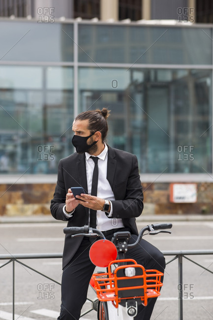 Portrait of businessman wearing protective face mask sitting on bicycle with smart phone in hands