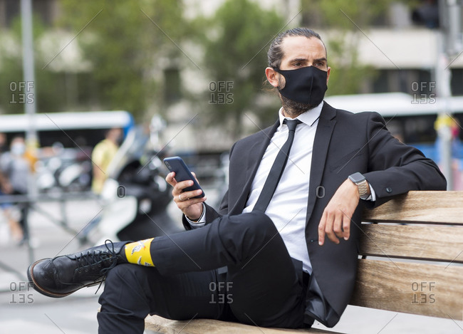 Portrait of businessman wearing protective face mask sitting on bench with smart phone in hand