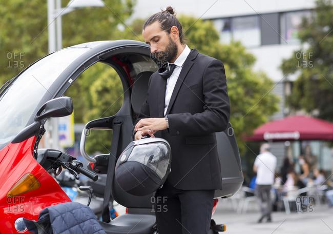 Bearded businessman putting on crash helmet before getting on motor scooter